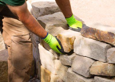 Handwerker beim Bau einer Trockenmauer aus Sandstein